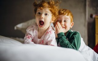 Little girl and her older brother are being silly for the camera in the morning. They are in their pyjamas in their mother's bed.